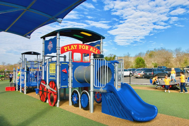 A jungle-gym style playset, shaped like a steam train, in a sunny park