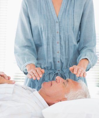 Therapist performing Reiki over face of man