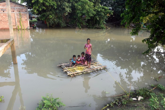 Children use a makeshift boat to cross the flood-affected area