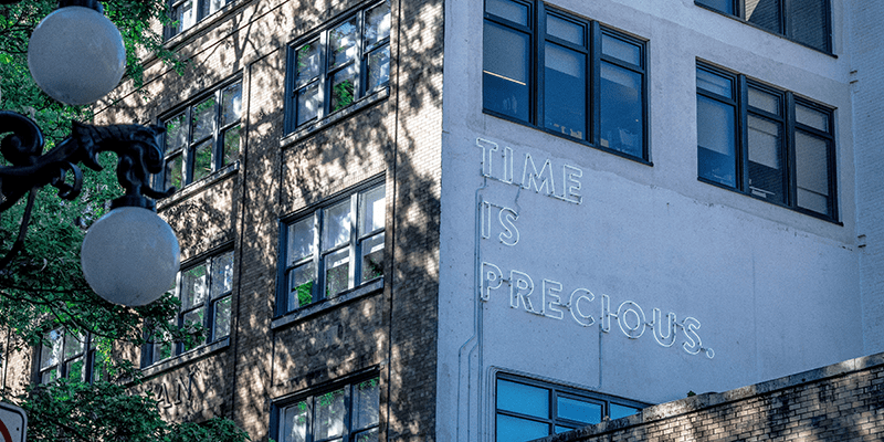 Time is precious - neon sign on the side of a building.