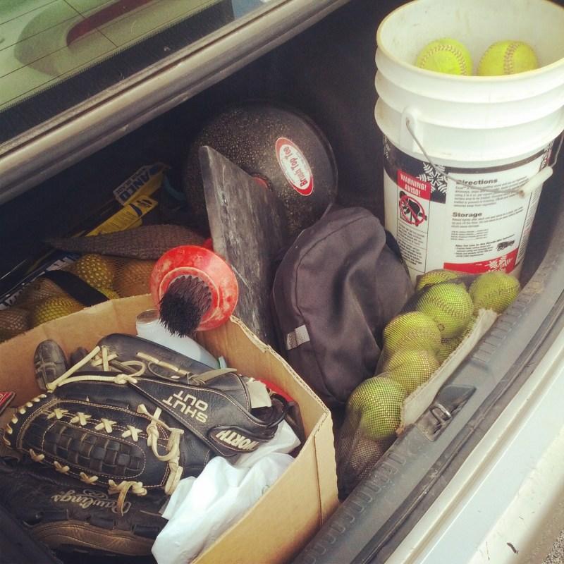 softball equipment in a car trunk