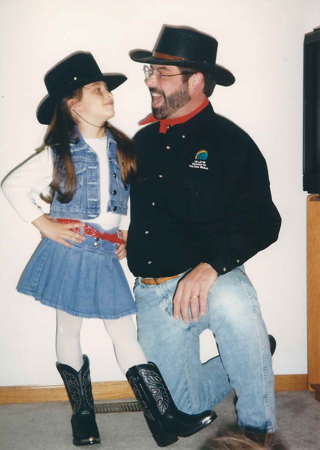 cowgirl standing next to cowboy father