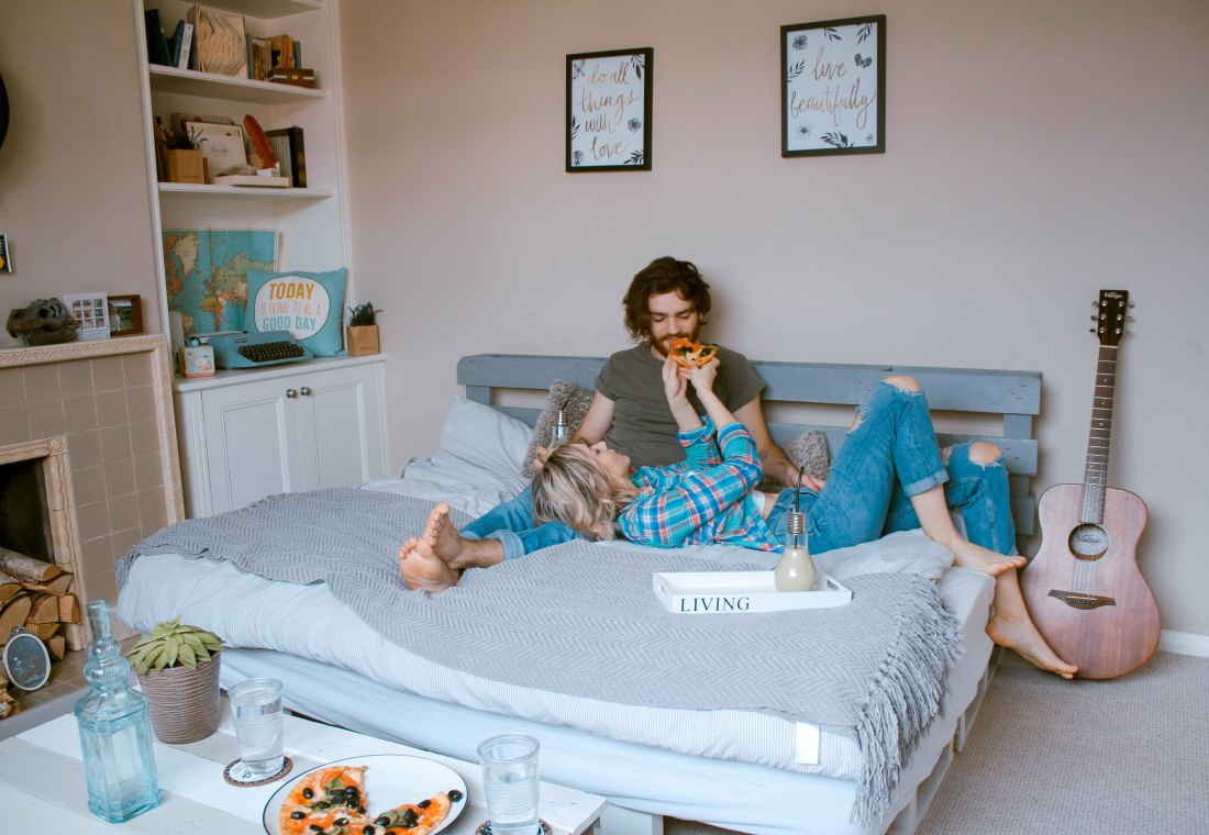 couple cuddling in bed and girl feeding guy pizza