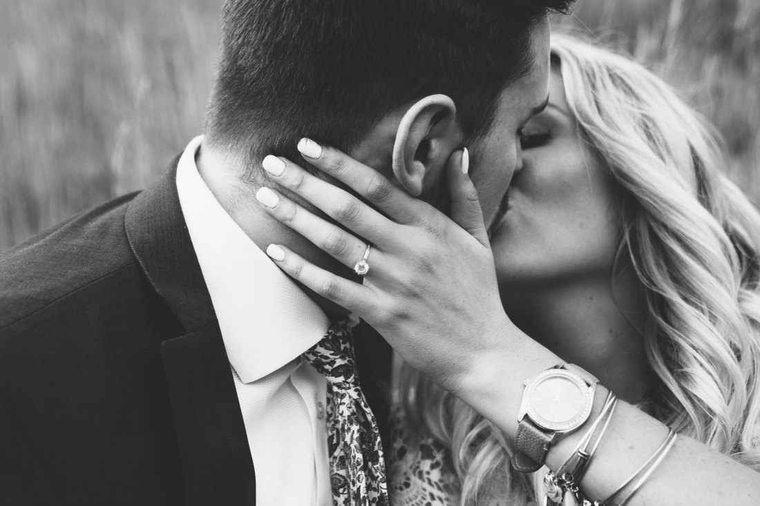 woman kissing man with wedding ring on