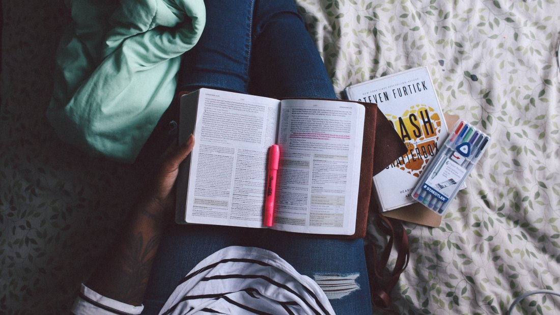 girl with bible and books on her lap