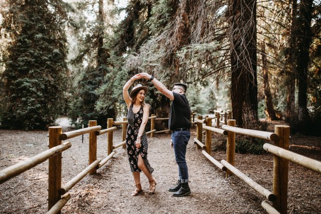 happy couple dancing on a bridge in the forest