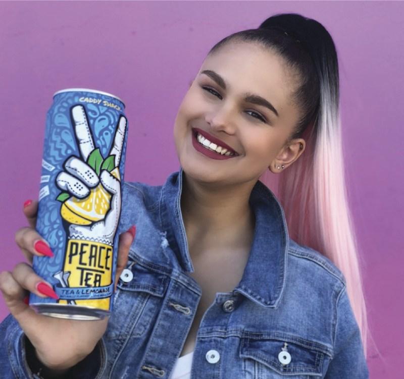 girl holding Peace Tea smiling