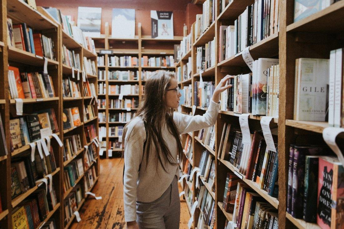 girl looking through bookshelves