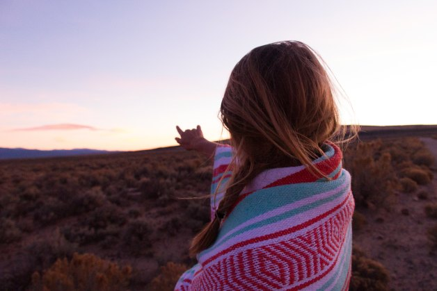 girl wrapped in blanket pointing at the sky and mountains