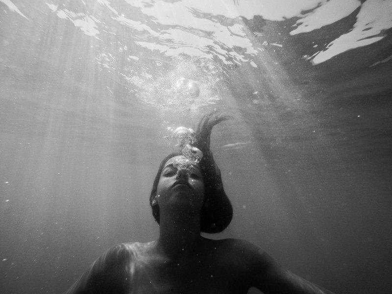 girl underwater blowing bubbles, sad