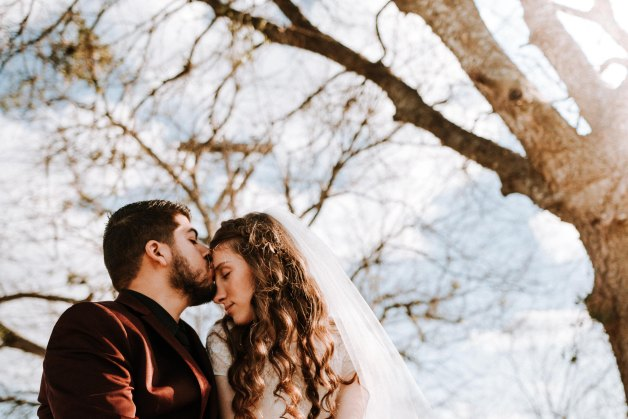 couple kissing under a tree