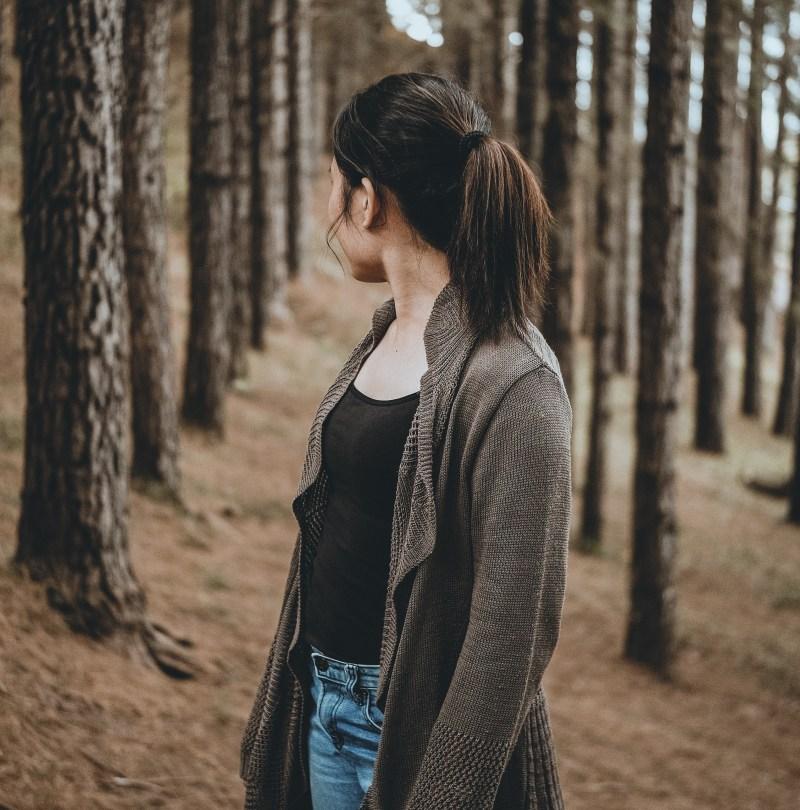 girl looking over her shoulder at forest