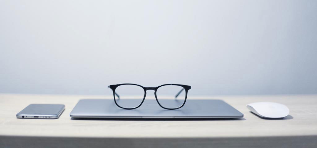 Glasses on top of a laptop
