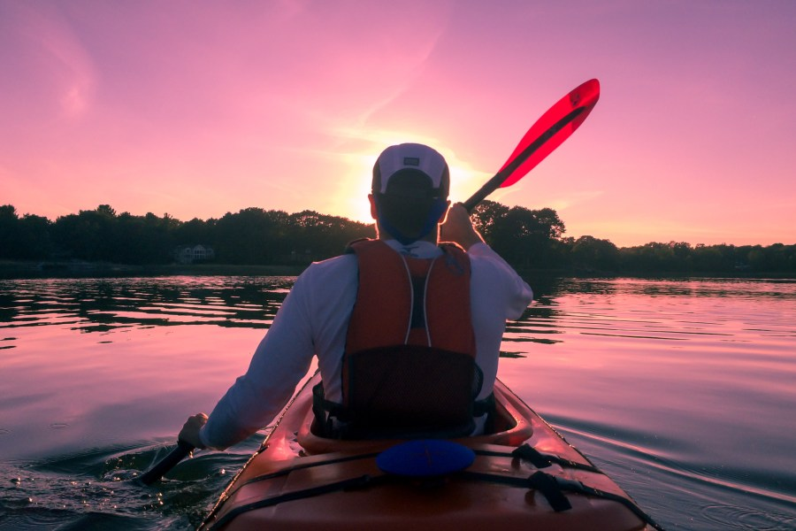Photo behind man kayaking into rising/setting sun.
