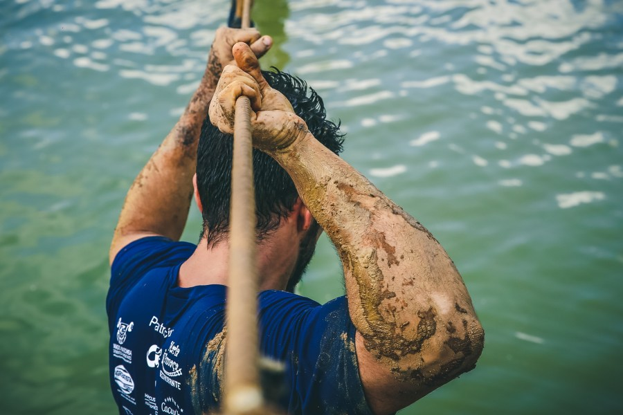 Mud spattered man in water holding rope overhead.