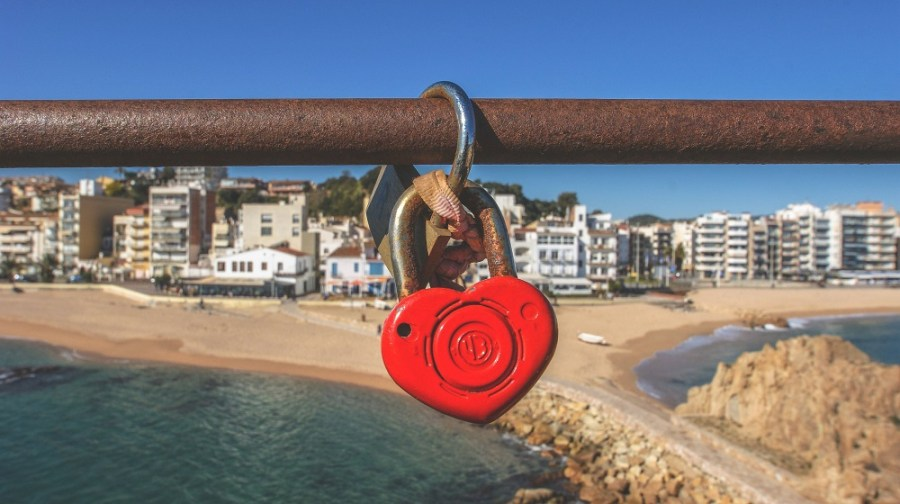 Heart-shaped lock hanging from a steel railing with a beach scene in the background