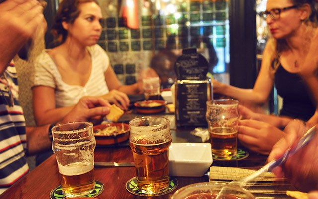 friends drinking beer and eating tapas