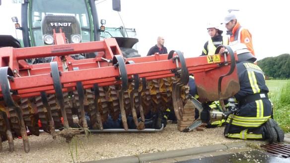 Rettung des eingeklemmten Mitarbeiters unter dem Vorbaugerät des Traktors