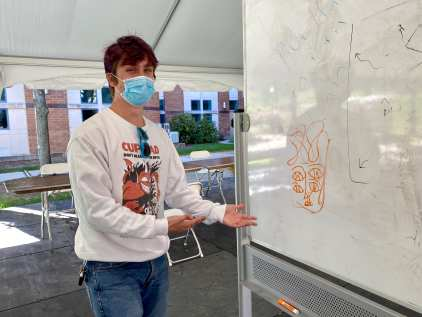 Eamon Sweeney doodles on the whiteboard at the Zoellner Arts Center COVID testing tent during the shoot on Sept. 20 in Bethlehem, PA. He shows off his final masterpiece. (J24/Julia D'Apolito)