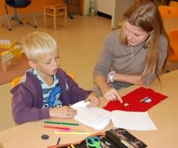 Pädagogin bei Arbeit mit Kind