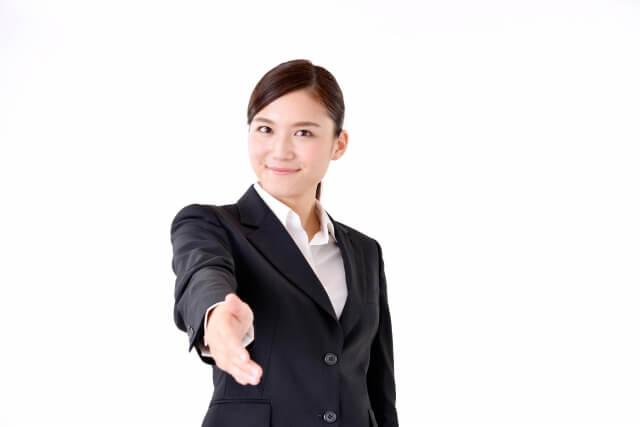 仲直りの握手を求め,右手を差し出すスーツ姿の女性