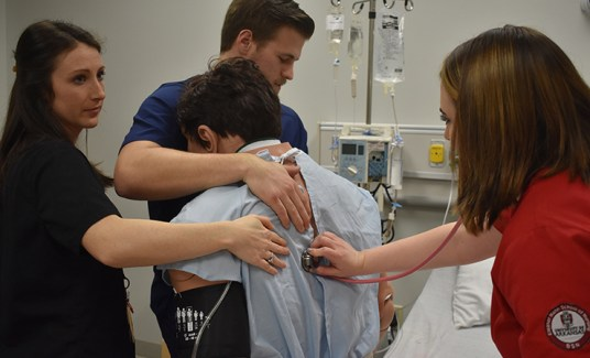 A nursing student checks a patient's vital sign while the physical therapy students assist.