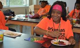 A PROMISE participant finishes her painting during an art class that was one of the camp's breakout sessions.