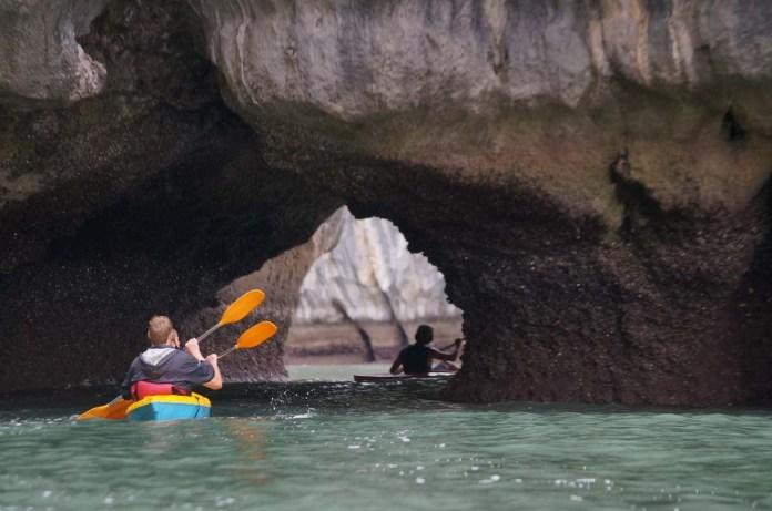 Paddling through karst arch, Lan Ha Bay