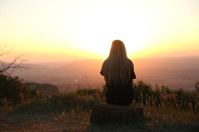 woman sitting on a mountain, sunrise