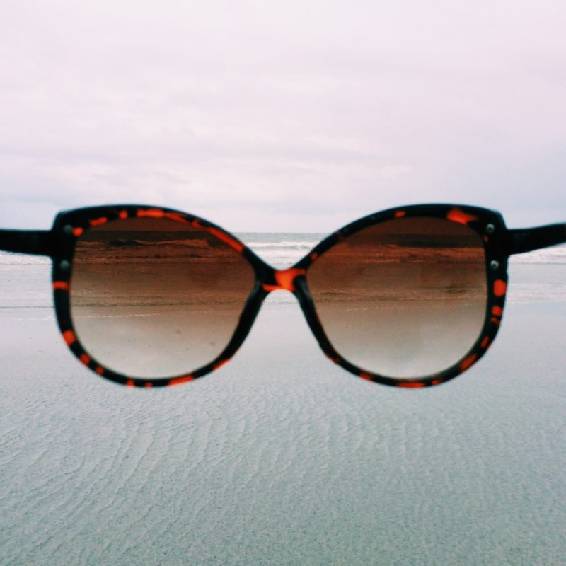Looking through sunglasses at the beach