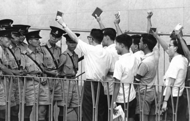 Protesters wave Mao's Little Red Book at police