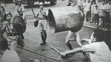 A protester hurls a rubbish bin at police