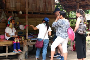 As they cannot speak much English, the Padaung women in Baan Tong Luang cannot properly explain their culture or their lives to the visiting groups. This job is left up to the Thai guide, and the women simply stare at the camera lenses pointed at them.