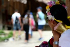 A woman watches tourists leave the village, having pocketed a handful of tips from the generous visitors.