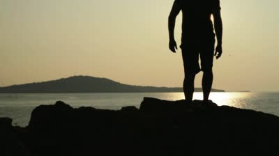 stock-footage-sunset-beach-silhouette-man-walking-lens-flare-hd