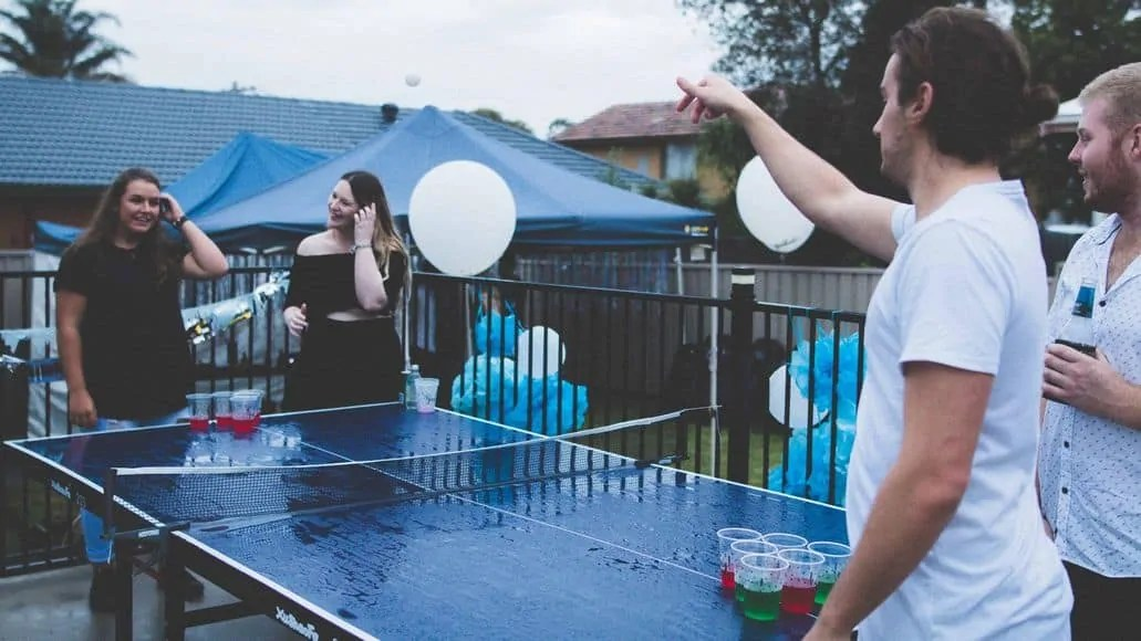 Four people playing beer pong