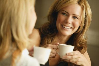 two girl friends chatting over a cup of coffee