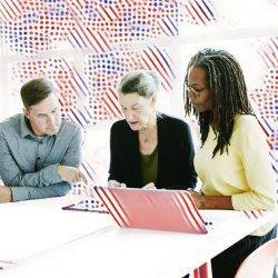 Three workers discuss a project around a table