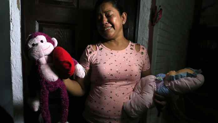 Rosa Ramirez sobs as she shows journalists toys that belonged to her nearly 2-year-old granddaughter Valeria in her home in San Martin, El Salvador, on Tuesday