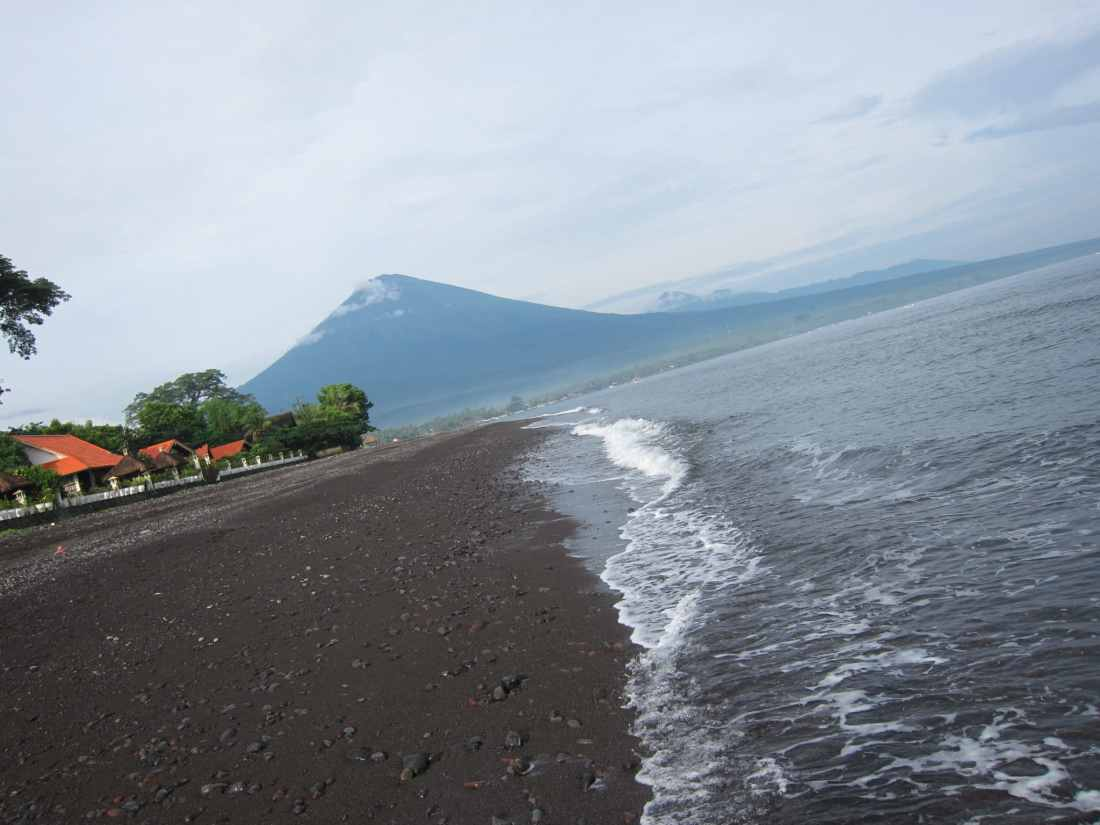 Amed black sand beach with view on Agung volcano Bali Indonesia