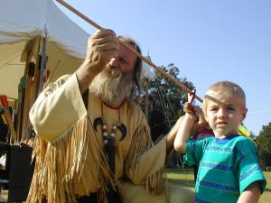 Man teaching child to hold atlatl