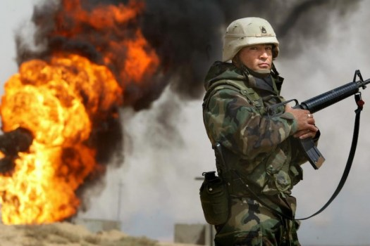 A U.S. soldier stands guard in March of 2003 next to an oil well at the Rumayla oil fields set ablaze by retreating Iraqi troops. (Photo by Mario Tama/Getty Images)