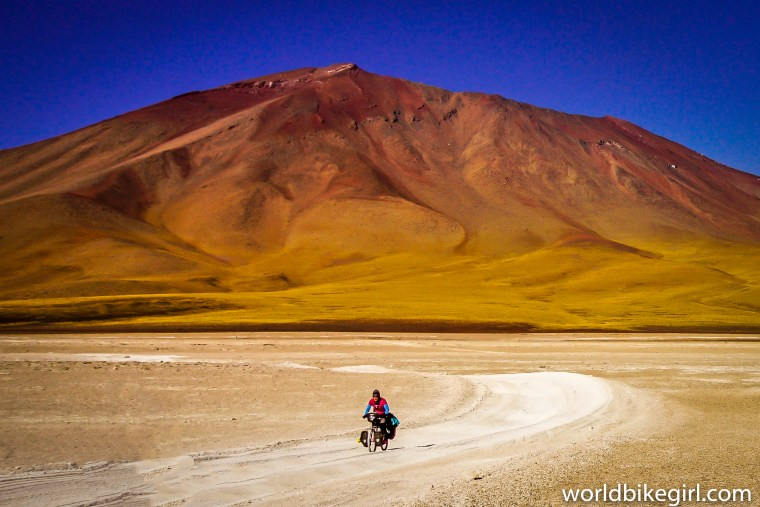 Photo of me cycling in the Altiplano in Bolivia with a mountain behind me