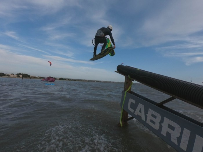 kiteboarder riding a slider in Sicily flatwater Italy features world class kiteboard academy grab