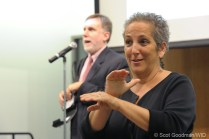 A man stands on stage and talks while a woman interprets