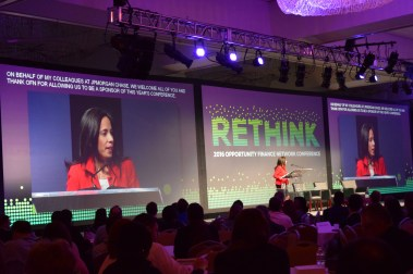 A woman stands on stage, flanked by two large screens, captions on both