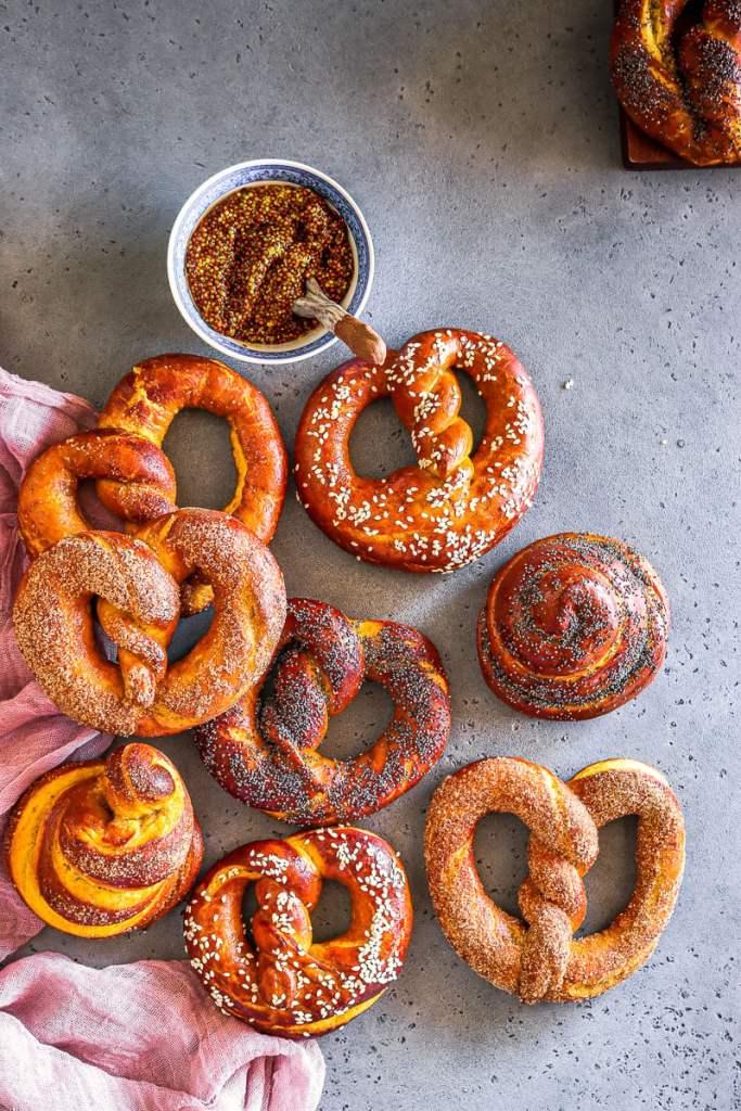 Pumpkin pretzels with different toppings alongside a mustard dip