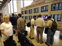 Photo: Passengers check the schedule board at the American ...