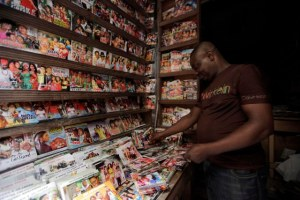 """In this photo taken  Wednesday, Feb, 5. 2014, a man arranges Nollywood DVD's in a shop in Lagos, Nigeria.  A 15-second drum roll and the title of the film, """"Deceptive Heart,"""" comes crashing onto the screen in a groovy 1970s font. Less than 10 minutes into the Nollywood movie, the heart of plot is revealed: A woman has two boyfriends and doesn't know what to do. The story moves as quickly as the film appears to have been shot. Some scenes are shaky, with cameras clearly in need of a tripod, and musical montages are often filled with pans of the same building. Most Nollywood movies are made in less than 10 days and cost about $25,000. (AP Photo/ Sunday Alamba)"""