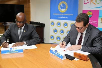 CTO secretary general Hugh Riley (left) and CDB president Dr Warren Smith sign partnership agreement at CDB headquarters